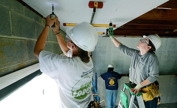 Kelli Panjehshahi of Hagerstown, left, and Mikaela Roach of Winchester, Va., secure a piece of fire resistent drywall to the ceiling of a garage on Woodpoint Avenue Women from Step Up for Women renovated a garage for Habitat for Humanity.