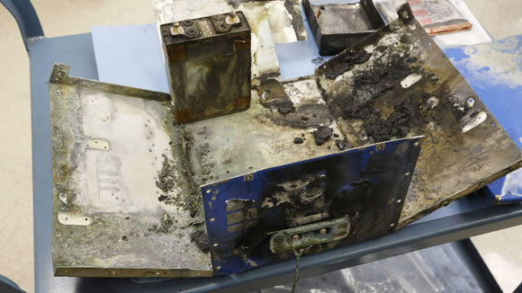 National Transportation Safety Board investigators display the exterior case of a thermal-damaged lithium ion battery, as a part of their ongoing investigation into why the battery caught fire in a Japan Airlines' 787 parked at Boston Logan International Airport Jan. 7.