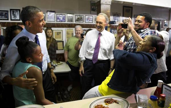Sean and Natalie Guthrie take photographs of their 11-year-old daughter Leilani's encounter with President Obama in Boston. Obama was among the Democrats stumping for Massachusetts Senate candidate Edward J. Markey, center.