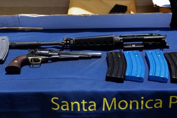 A table of evidence collected in the Santa Monica shooting investigation includes a .44-caliber handgun and the upper receiver of an AR-15-style rifle.