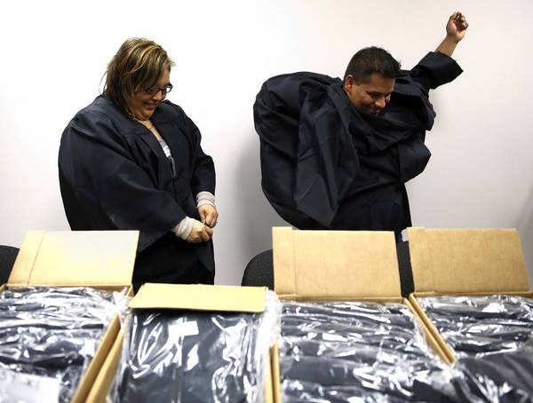 Nanci Bautista, left, and husband Marco Salse try on their gowns for their upcoming graduation ceremony Friday, where they will celebrate having earned their GED certificates.