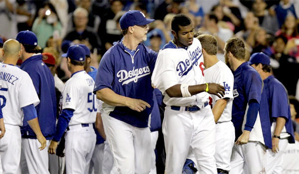 Dodgers hitting coach Mark McGwire escorts right fielder Yasiel Puig away from the fighting after a bench-clearing brawl erupted after pitcher Zack Greinke was hit by a pitch in the seventh inning on Tuesday.