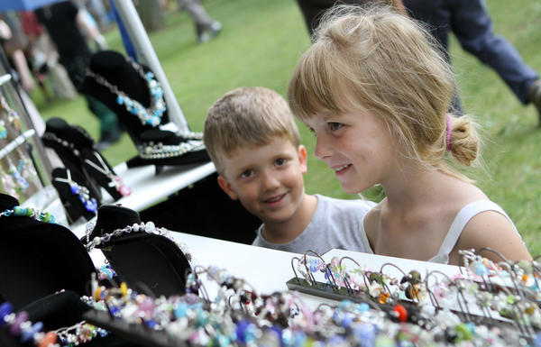Children admire jewelry on display at the Leeper Park Art Fair in South Bend. (South Bend Tribune/BARBARA ALLISON)