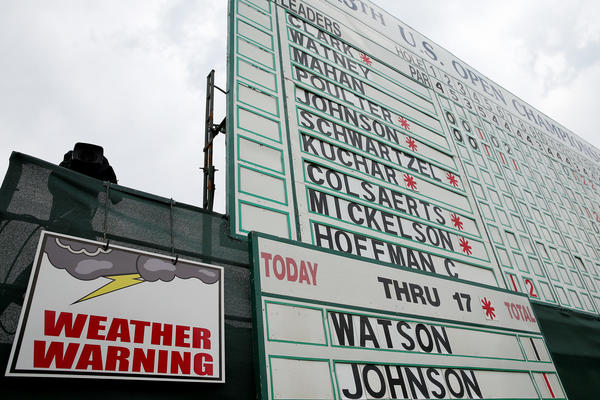 A weather warning sign is seen on the a leaderboard on the 18th hole during Round One of the 113th U.S. Open.