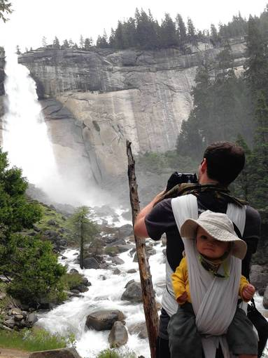 A hiker photographs Nevada Falls along the Mist Trail in Yosemite National Park with a baby on his back.