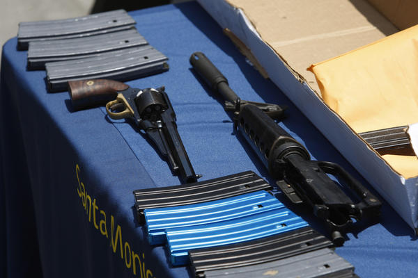 A pistol, part of an AR-15 type of gun and ammunition allegedly used during a mass shooting are displayed at Santa Monica Police Department headquarters.