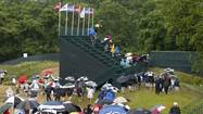 Fans under umbrellas wait out a weather delay during the first round of the 2013 U.S. Open golf championship at the Merion Golf Club in Ardmore