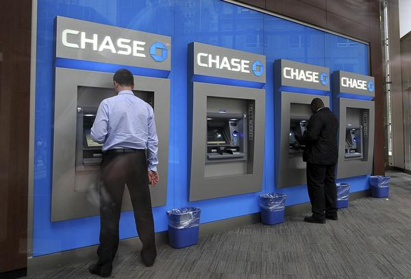 Federal authorities have charged eight men with conspiracy to commit wire fraud by hacking into the networks of banks, including JPMorgan Chase. Above, ATMs at a Chase branch in New York.