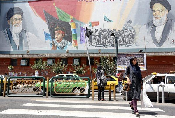 Iranians walk past a huge billboard depicting Supreme Leader Ayatollah Ali Khamenei, left, and late Supreme Leader Ayatollah Ruhollah Khomeini in Tehran on Thursday, the last day of campaigning before Friday's presidential election.