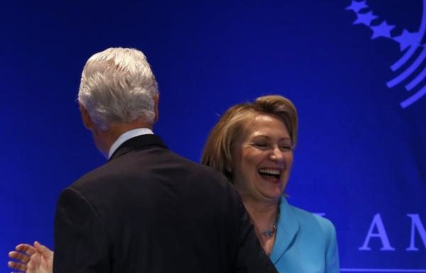 Former U.S. Secretary of State Hillary Clinton shares a laugh with her husband, former U.S. President Bill Clinton, at the Clinton Global Initiative America meeting in Chicago Thursday.
