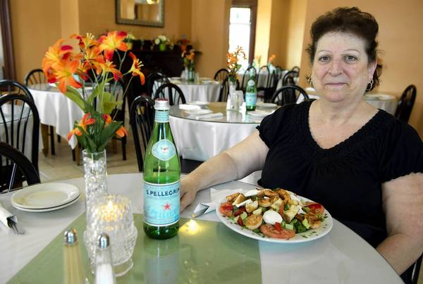 Server Linda Sherlock with a special salad with roasted peppers, fresh mozzarella, grilled shrimp, tomatoes and homemade croutons at Carmen's Italian Family Restaurant in Catasauqua.