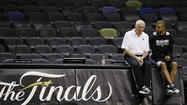 San Antonio Spurs coach Popovich sits with player Parker during practice for their NBA Finals basketball playoff series in San Antonio