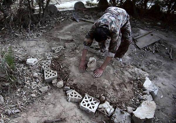 A Free Syrian Army fighter works on the grave of a fellow fighter who he said died in an explosion from a bomb planted by the Syrian regime in Deir al-Zor.