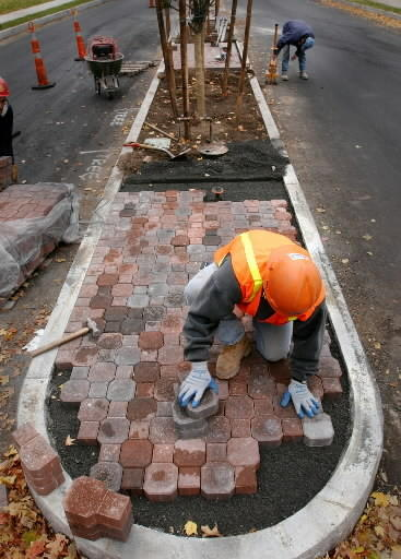 In this 2002 photo, a construction worker places brick pavers in a median on Farmington Avenue between Four Mile Road and Mountain Road. Major road reconstruction will begin soon on Farmington Avenue on the other side of West Hartford center, from Trout Brook Drive to Armore Road.