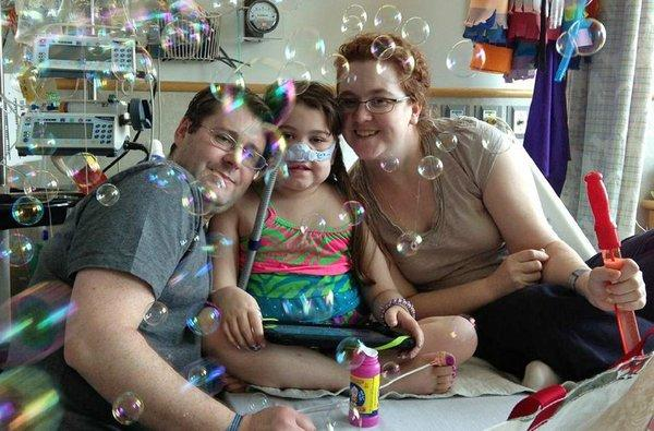 Sarah Murnaghan, center, celebrates the 100th day of her stay in Children's Hospital of Philadelphia last month with her father, Fran, left, and mother, Janet.