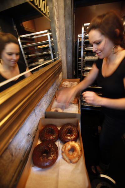 A worker takes orders of doughnuts and coffee at the Doughnut Vault in Chicago on Thursday, May 31, 2012.