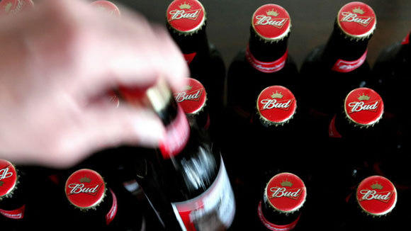 A bottle of Budweiser beer is lifted from a shelf at a pub in Hornchurch, Essex, in a 2008 file photo.
