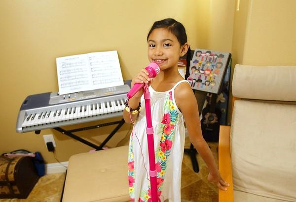 Sydney Haik, 7, goofs around on her plastic mic in her home studio. She will sing the national anthem to open this weekend's Fete de la Musique in Laguna Beach.