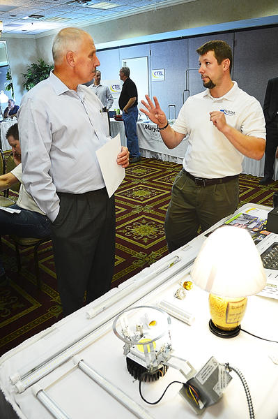 Edward Holier of McShea Management, Inc. of Gaithersburg, Md., left, gets a description of LED technology from Daystar Lighting Solutions CEO Stan Barrett Thursday at the 2013 Potomac Edison Customer Workshop and Trade Ally Seminar at the Ramada Plaza in Hagerstown.