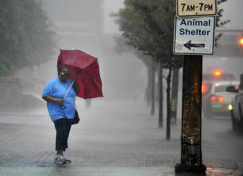 A pedestrian struggles with her collapsed umbrella as she tries to cross Lombard Street at Light Street during a severe thunder storm that passed through downtown Baltimore. The storm caused a heavy downpour during the evening rush hours.