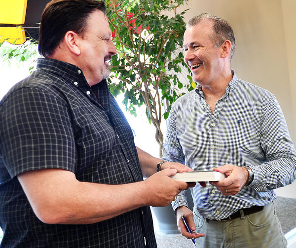 """Retired British Royal Navy Lt. Cmdr. Howard Leedham, right, signs a copy of his book, """"Ask Forgivemess Not Permission: The True Story of an Operation in Pakistan's Badlands"""" for Sean Guy of Greencastle, Pa., Thursday at the Visitors Welcome Center in Hagerstown's Public Square."""