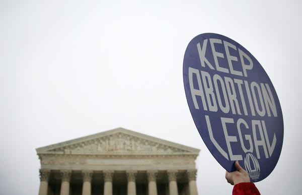 A pro-choice demonstrator holds up a placard outside the U.S. Supreme Court in Washington, D.C.