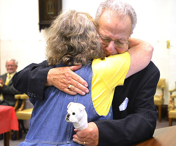 Berkeley County Clerk John W. Small Jr. hugs his friend MaryAnn Ferro Thursday during a ceremony in which Small was recognized for his long service to the county. A new flagpole in front of the downtown courthouse is dedicated to him.