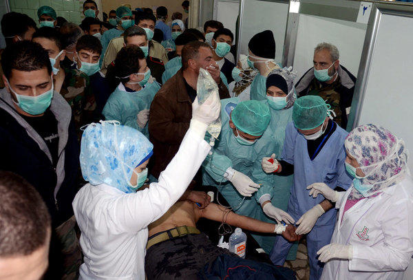 In this Tuesday, March 19, 2013 file photo released by the Syrian official news agency SANA, a Syrian victim who suffered an alleged chemical attack at Khan al-Assal village according to SANA, receives treatment by doctors at a hospital in Aleppo, Syria.