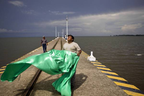 A worker prepares a flag to hang on a wharf at Lake Nicaragua. A Hong Kong company won the concession to build and operate the Nicaragua canal, which is expected to include the lake.