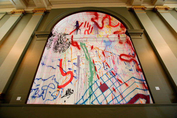 Runaway, 2013, by Sarah Cain, an acrylic, vinyl and string on window and wall, is on display at Painting in Place sited in the Farmers and Merchants Bank on Main St. in Downtown Los Angeles.