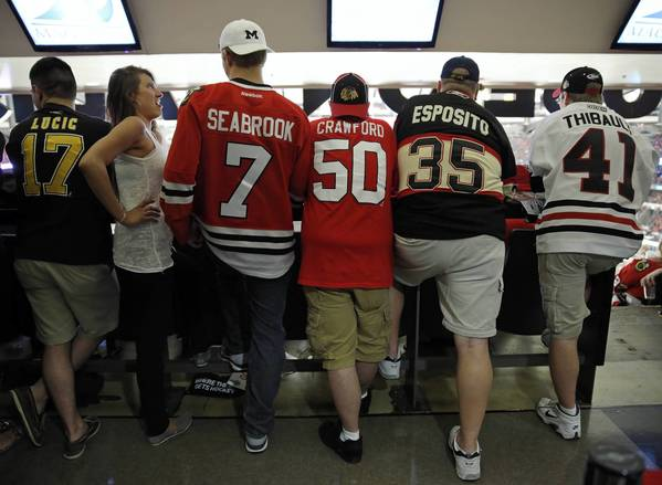 A woman turns away from a Boston Bruins fan and toward a group of Blackhawks fans Wednesday in the first period of Game 1 of the Stanley Cup Final at the United Center in Chicago.