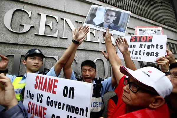 Demonstrators hold signs supporting Edward Snowden on Thursday outside the Consulate of the United States in Hong Kong as they urge the U.S. government to pardon the 29-year-old former contractor.
