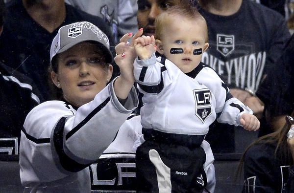 A fan holds has her baby knocks on the glass during a playoff game between the Kings and Sharks at Staples Center.