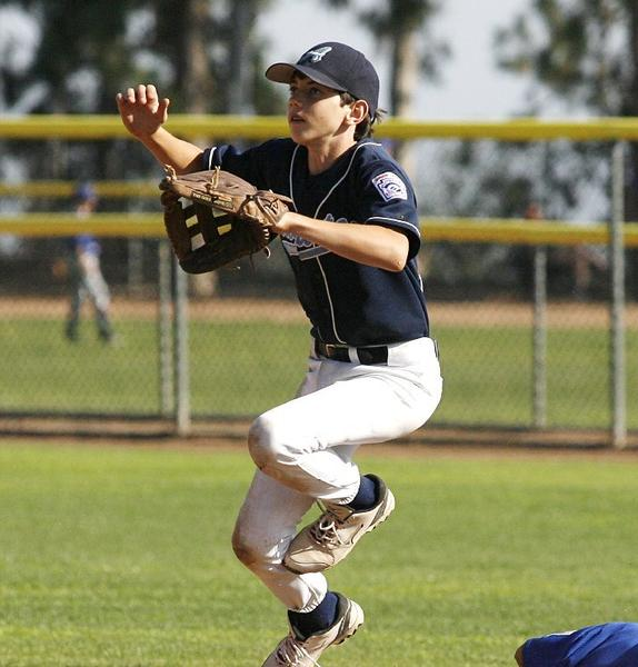 Crescenta Valley Junior Augusta's Drew Atherton jumps over Burbank Junior Cubs' Matthew Shaugabay in a 2-0 CV win.
