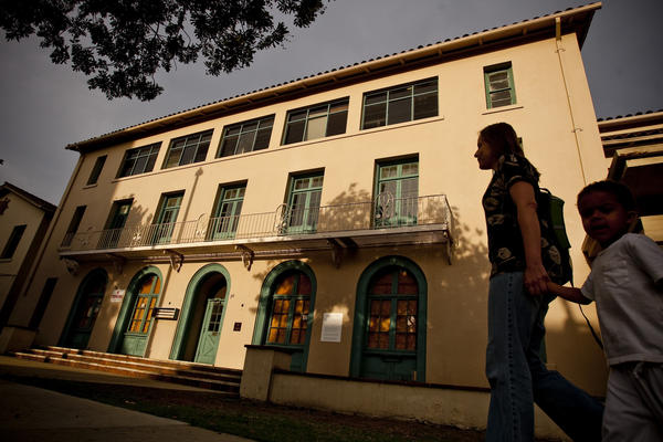 A women and a child walk by the long-shuttered YWCA in Pasadena.