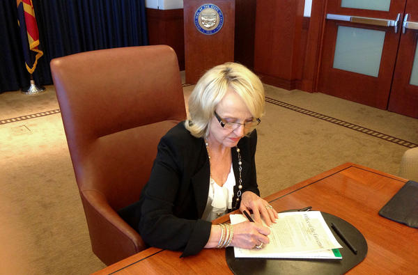 In this photo provided by by Arizona state Rep. Jeff Dial, Gov. Jan Brewer signs a proclamation calling the Legislature into special session Tuesday to take up a proposal to expand Medicaid.
