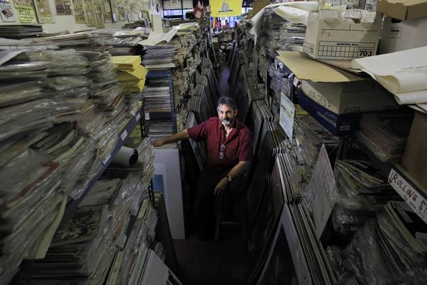 "Bob Katzman poses in his Skokie business, The Magazine Museum, which he calls his ""paper prison."" He has thousands of vintage magazines, and very few customers."