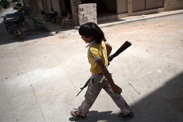 A Syrian boy carries an old rifle to rebel fighters in the the town of Maaret al-Numan.
