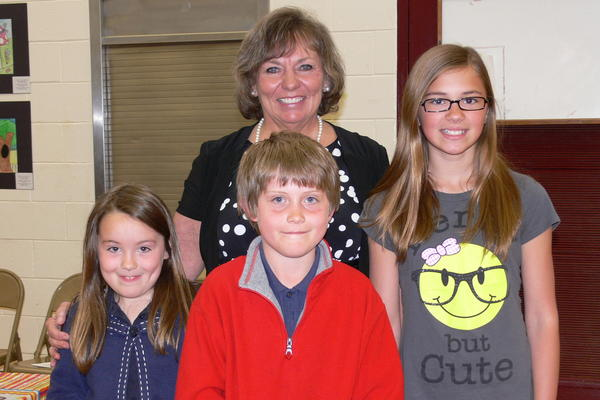 Peggy Brennan (back), Charlevoix Area Garden Club president, is shown with state level garden poster contest winners (from left) Catherine Hayes, Joshua House and Emmaline Peterson.