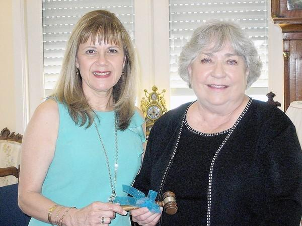 Las Candelas retiring President Monica Sierra, left, hands gavel to new President Jeannie Flint.