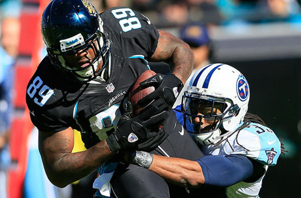 Jaguars tight end Marcedes Lewis tries to fight through a tackle by Titans defensive back Michael Griffin during a game last season.