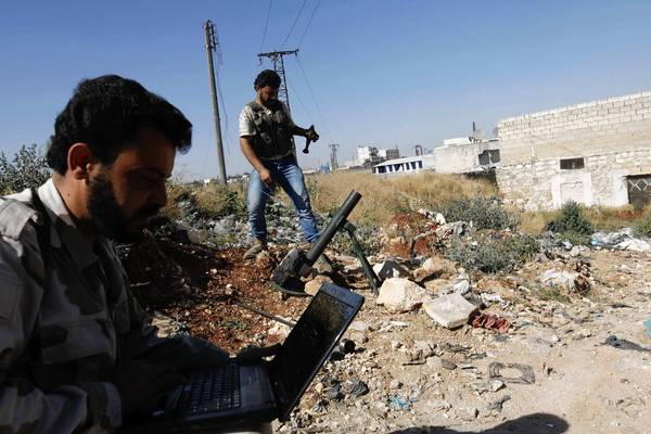 A Free Syrian Army fighter uses a laptop as another prepares to fire a mortar launcher at the frontline near Nairab military airport, which is controlled by forces loyal to Syria's President.