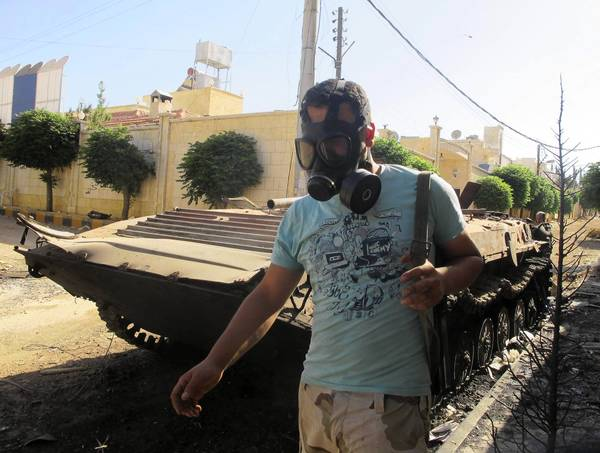 A Free Syrian Army fighter wearing a gas mask carries his weapons Thursday as he walks past a damaged tank near Idib.