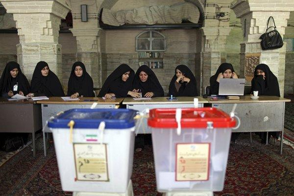 Iranian election workers await voters Friday at a polling station in Qom.