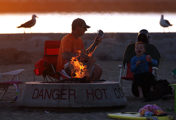 Dave Osinga and his son Zachary, 6, sit by the fire as the sun sets at Corona Del Mar State Beach.