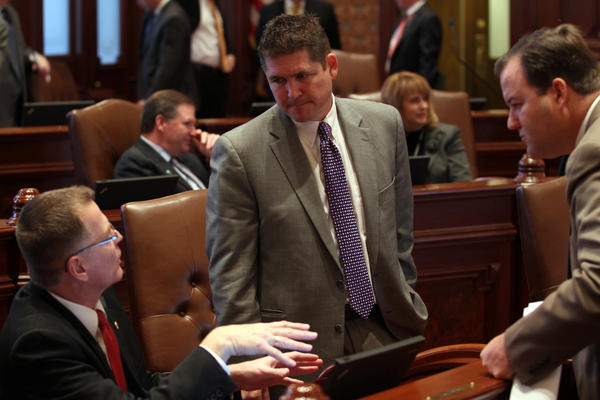 State Sen. Kyle McCarter, R-Lebanon, center, talks with colleagues on the Senate floor during the first day of the Veto Session Tuesday, Nov. 26, 2012 at the Capitol in Springfield.