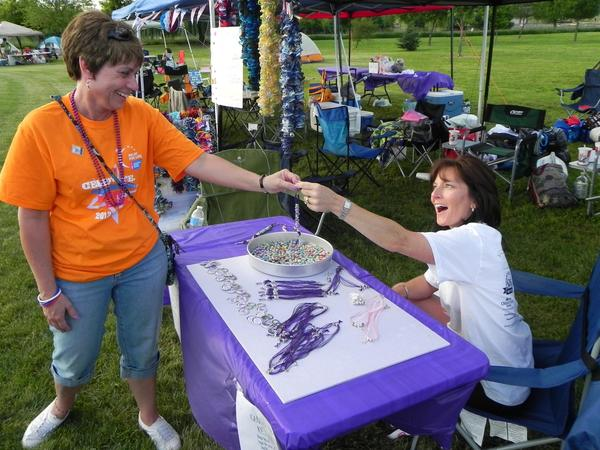 Katina Engles of York, Pa., gives Becky Mull of Chambersburg, Pa., the lap bead key chain she completed for her at the American Cancer Society's 10th Annual Chambersburg Relay for Life at Norlo Park in Fayetteville, Pa., Friday.