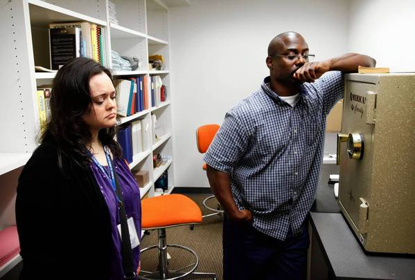 Santa Monica College lead library assistant Jan Juliani and computer support specialist Myron Kabwe revisit the storage room where they herded seven others to hide from a gunman, who shot into the room.