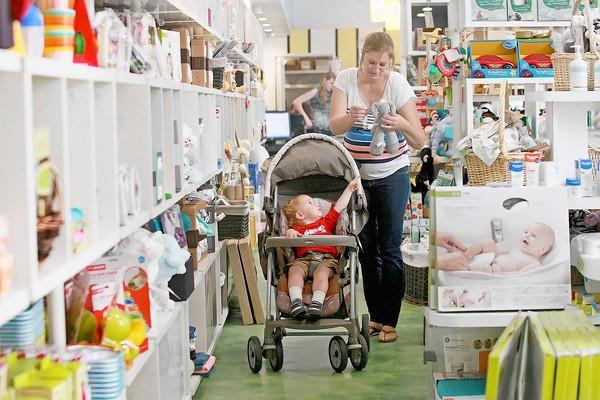 Chelsea Fisher, of Huntington Beach, accompanied by her 18-month-old son Derenger, looks for a gift as she shops at Bel Bambini for her friend's baby on Thursday.