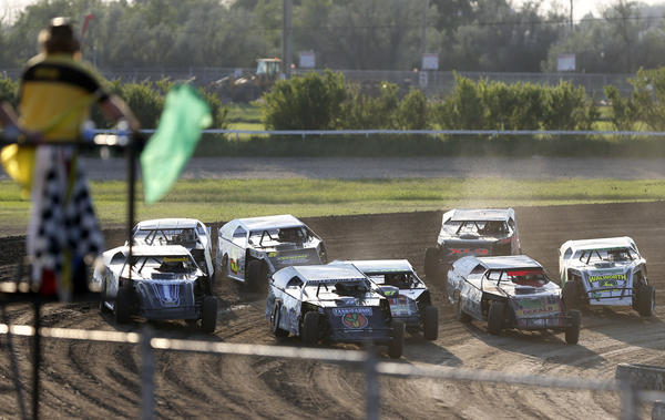 Flagman Jason Schaunaman, foreground left, drops the green flag on the second heat of modified action Friday night at the Brown County Speedway.